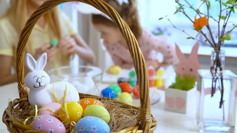 Happy Easter! Young mother and her cute little daughter wearing funny rabbit ears are coloring easter eggs sitting at a festive table with basket and Bunny