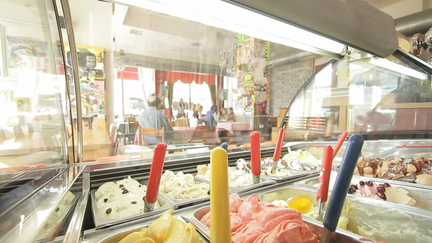 looking at a coffee shop interior through an ice cream display window
