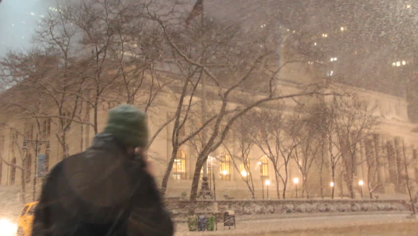 Heavy Snow falling in front of the public Library on 42nd and 5th in New York City during the evening in the middle of winter