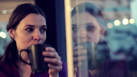 Sad, depressed woman drinking tea by the window in home
