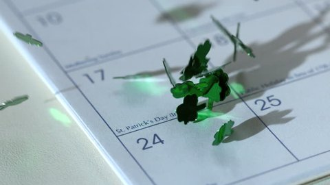 Shamrock confetti falling on calander in slow motion marking st patricks day