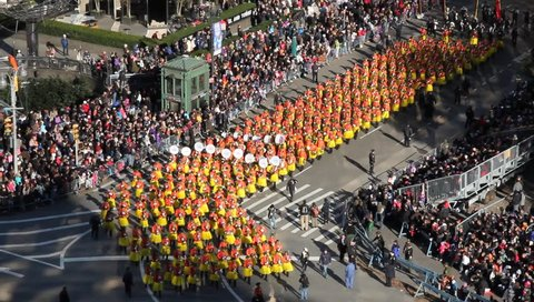 New York, NY - Circa 2011: Marching Band in Yellow Skirts turn corner as they march past an attentive crowd during the Macy's Thanksgiving day parade