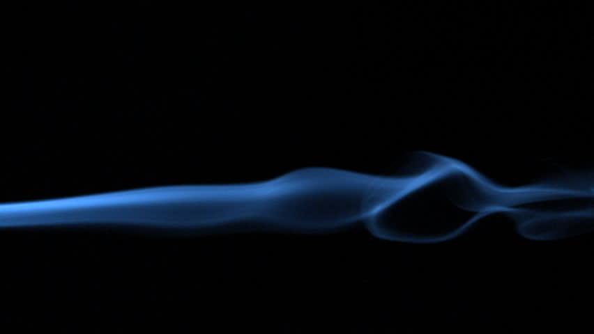Blue smoke blowing across black background in slow motion