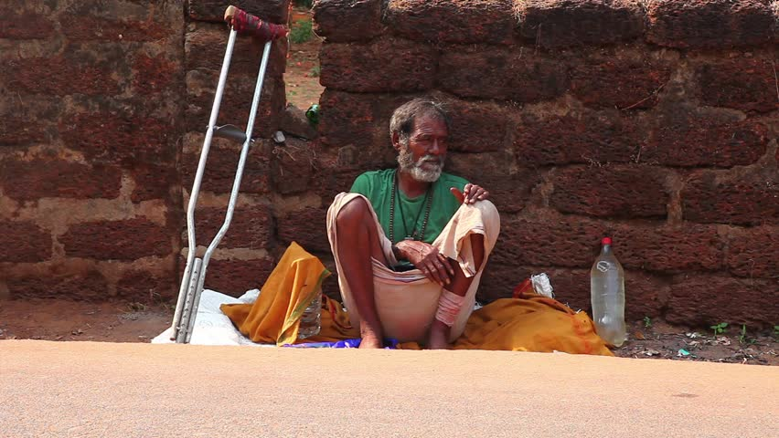 CALANGUTE, INDIA - MARCH 11, 2013: Homeless man sitting on the ground and waiting for alms from passers-by. on March 11, 2013 in Calangute, India