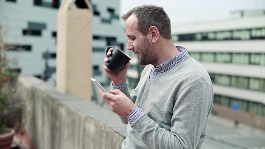 Young man drinking coffee and using smartphone on terrace