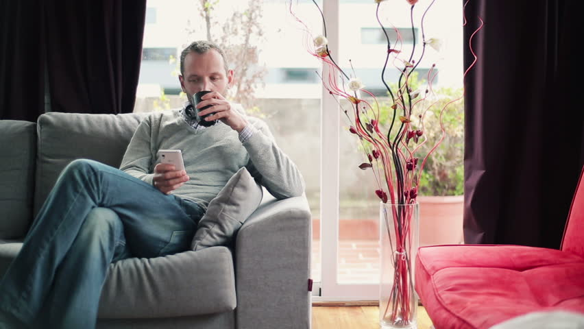 Young man drinking tea and using smartphone on sofa at home