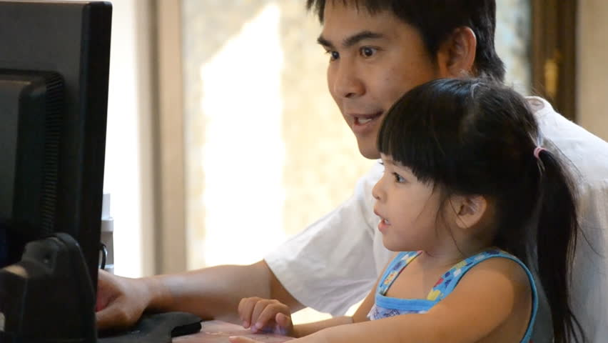 asian father teach cute daughter how to use computer