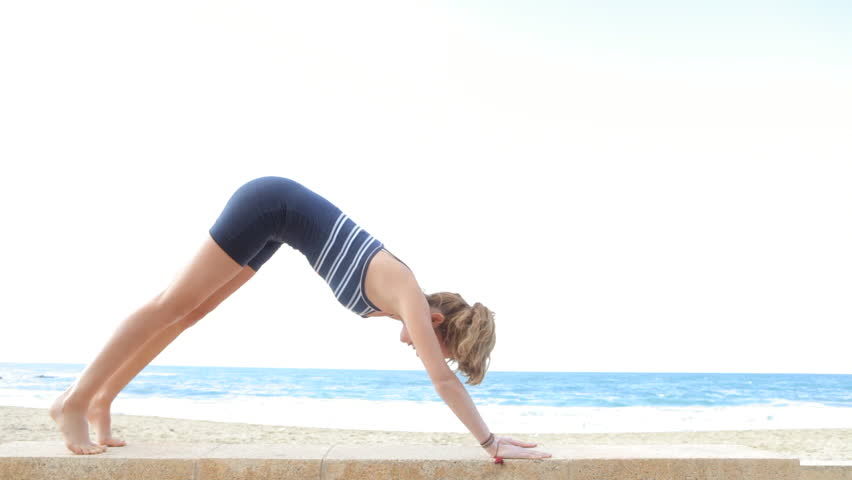 Side view of an attractive young woman doing yoga on a beach and stretching her body wearing a sport body.