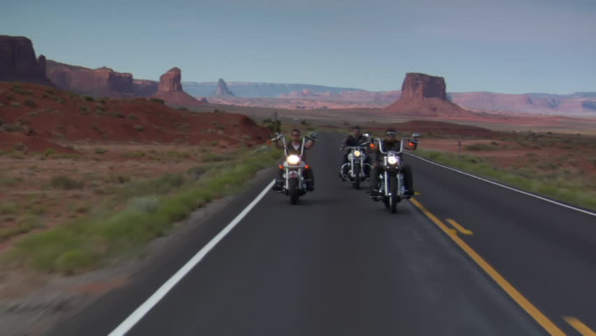 Three bikers on a winding open desert highway