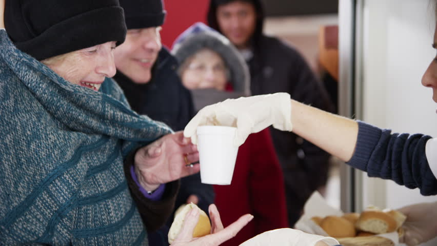 Friendly voluntary workers standing at a soup kitchen serving hatch are handing out cups of hot soup and bread to a waiting line of homeless and needy people.