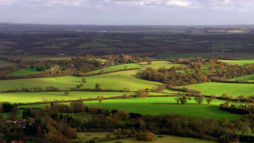 Stunning aerial shot over lush green fields and meadows in the English countryside. It is a clear, bright autumn day and the sun is shining.