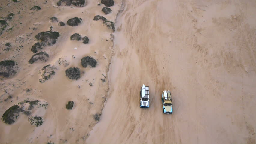 AERIAL: cars in a dry riverbed