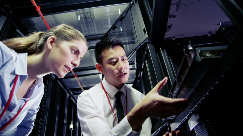 Two IT engineers are working in a data center with rows of server racks and super computers. They are discussing their work as they check cables and other equipment.  | Shutterstock HD Video #3590018