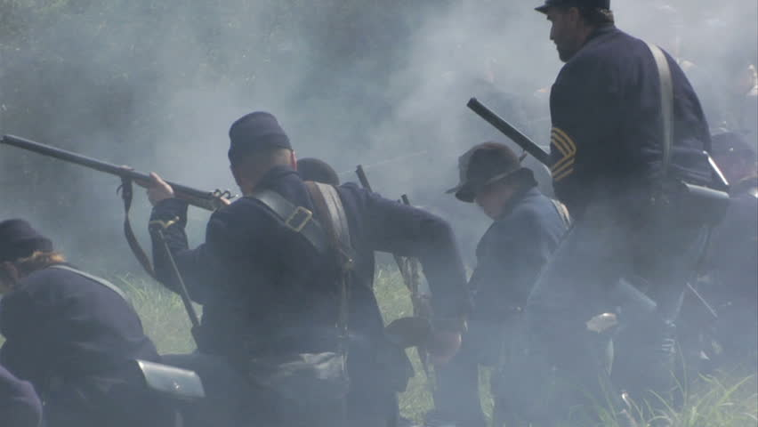 GEORGIA - OCTOBER 2008 - large-scale, epic Civil War anniversary reenactment -- in the middle of battle.  Union dismounted Cavalry on the smoky firing line as cannon fires behind them.  Battle smoke.