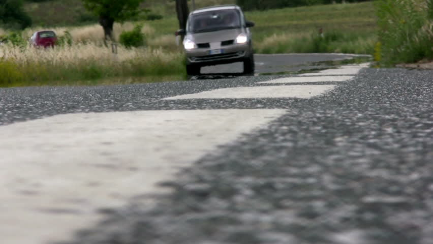 Asphalt road in the countryside. A hot day. Cars and motorcycles passing on the