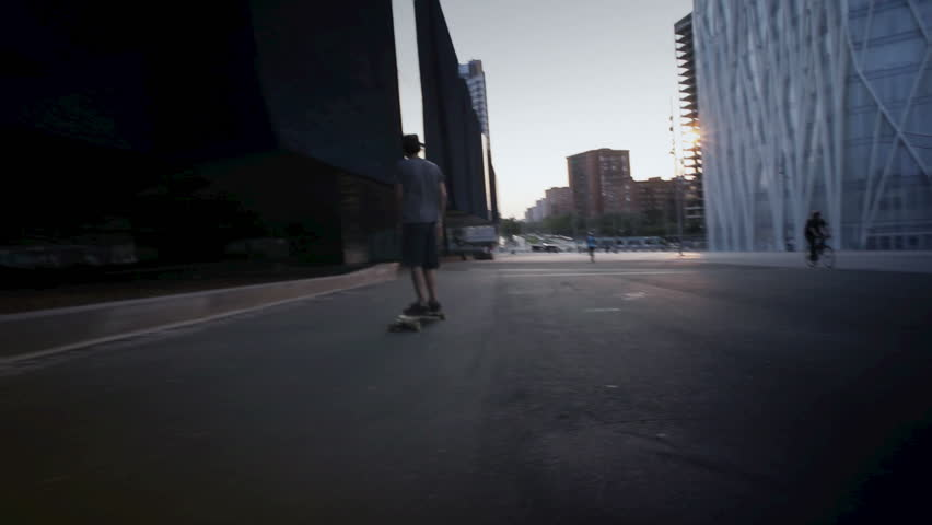 Young guy with skateboard on urban hill during a nice sunset