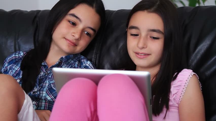 Two happy teenage girls having fun using tablet computer