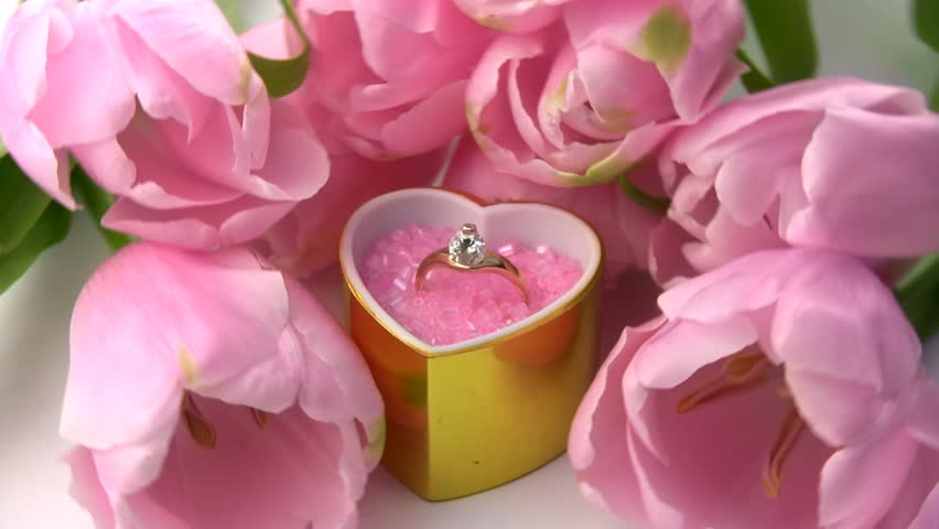 A golden ring with precious stones in gift box as a heart, surrounded by fresh