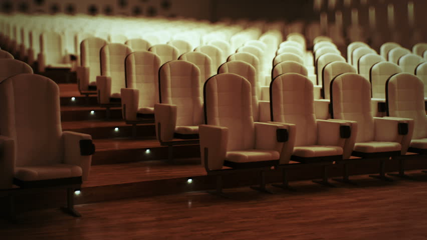 Large empty cinema with comfortable leather seats.