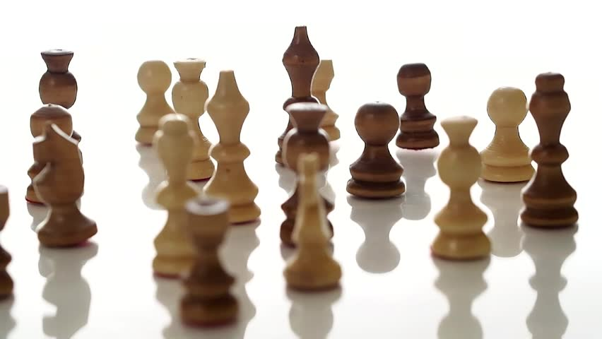 Wooden chess pieces rotating on a white studio background.