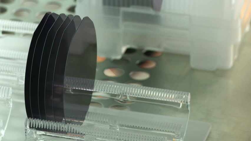 Detail view of silicon wafers being prepared to go into a kiln as part of a manufacturing process in a clean room.