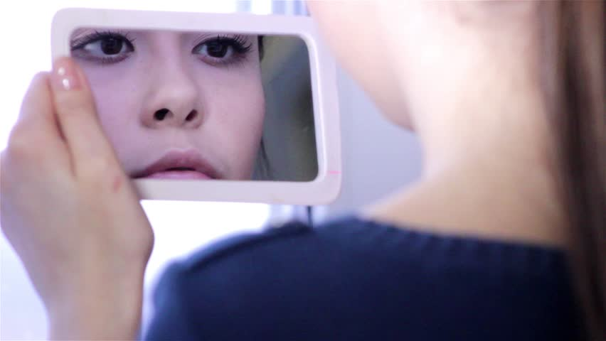 Young woman doing makeup in front of a mirror, full face, blurred background.Beautiful  young girl is doing makeup.Young woman with mirror and makeup brush.