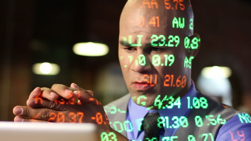City trader watches the market and trades with his smart phone and laptop as
