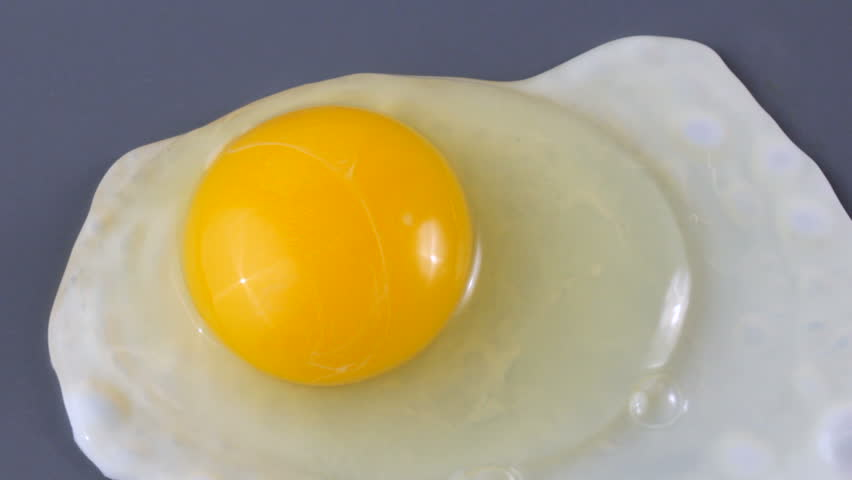 Close up of hands breaking egg over griddle, cooking sunny side up