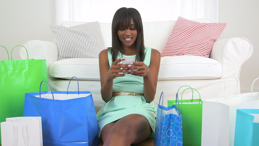African American woman with shopping bags texting on mobile phone