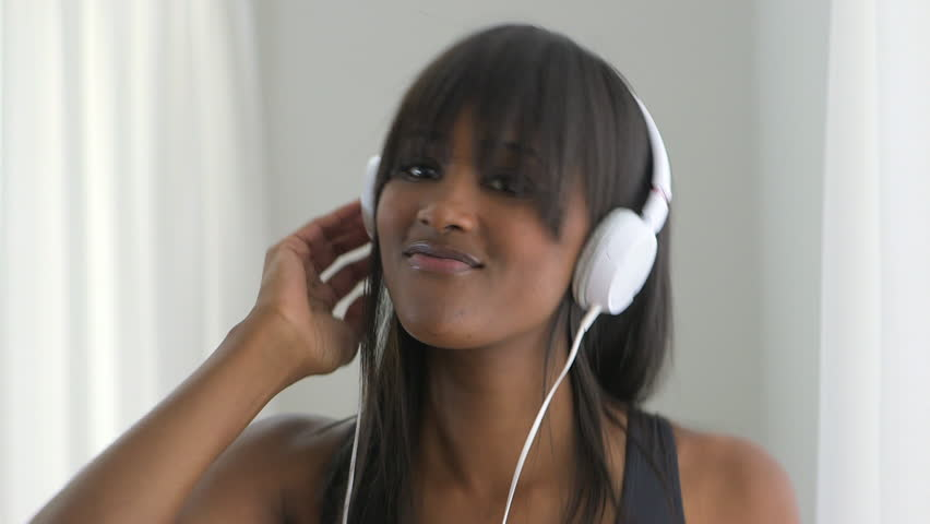 African American woman listening to headphones and dancing
