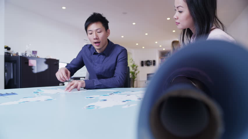 Attractive asian business man and woman are working in a light and modern open plan office. They are looking at a map of the world and discussing possibilities for future business ventures.