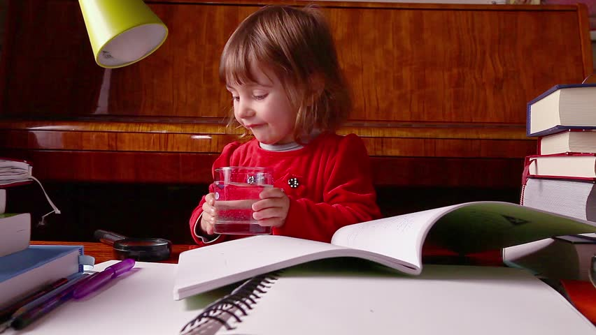 Little baby girl looks through a magnifier lens to a glass of water and is surrounded by books and other educational items.