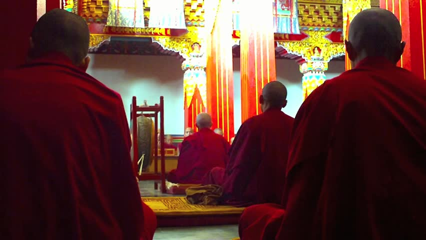 A group of monks sit and chant prayers in a monastery high in the Himalayas.