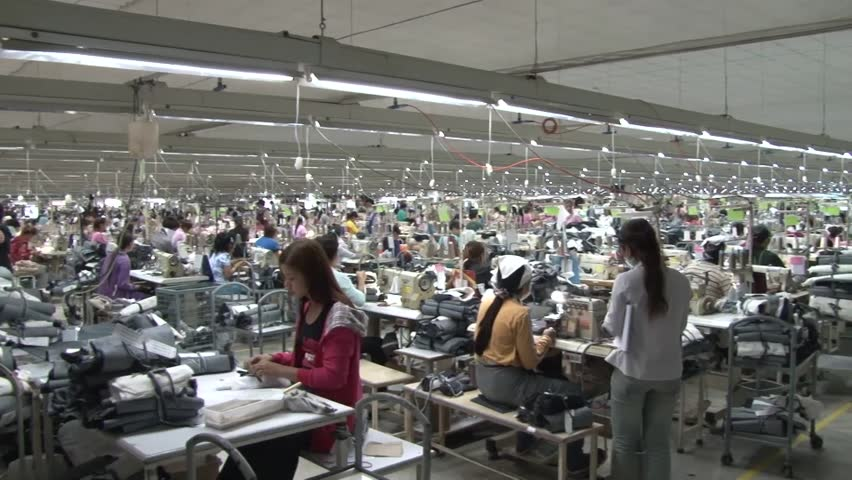 PHNOM PENH, CAMBODIA - CIRCA SEPTEMBER 2011 - excellent wide shot pan from left to right inside active garment factory, with hundreds of unidentified garment workers