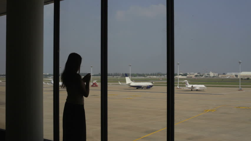 Girl speaks by a mobile phone at the airport