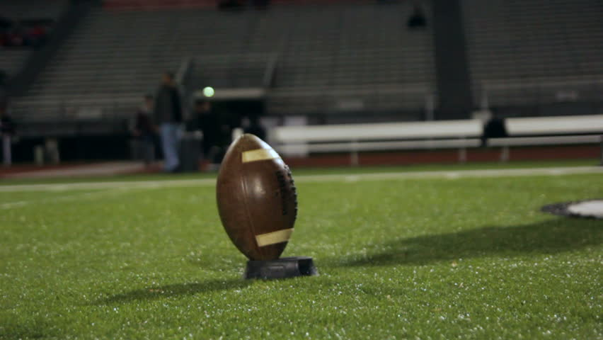 Football player practicing kicking off, on a turf field at night.