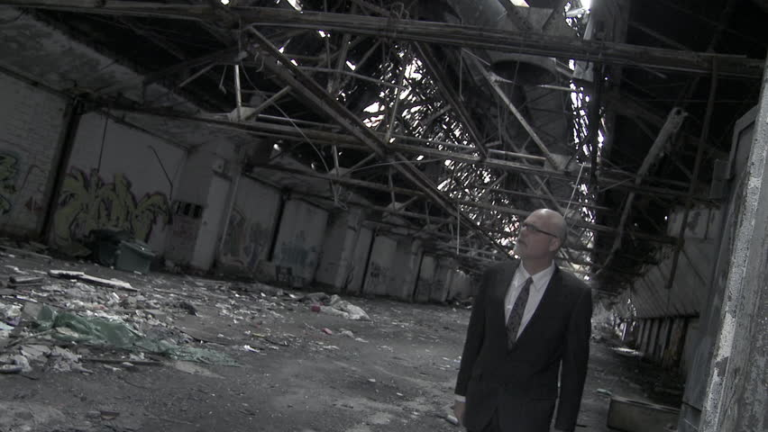 Well-dressed businessman walks into a crumbling former industrial building and
