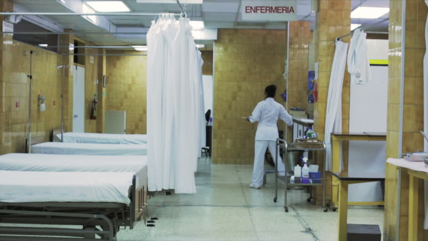 Nurse cleans the beds in the er room of an hospital in Latin America.