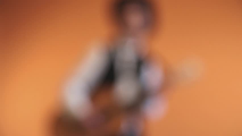 Retro fifties western rock and roll musician with black cowboy hat playing acoustic guitar. Studio shot. (No audio).