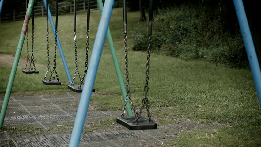 DOLLY: Deserted swings in a playground