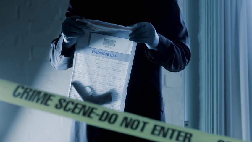 Detective puts gun into evidence bag