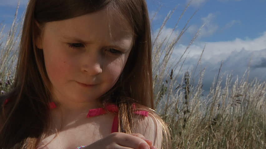 Little girl in meadow with a painted lady butterfly sitting on her hand before flying off