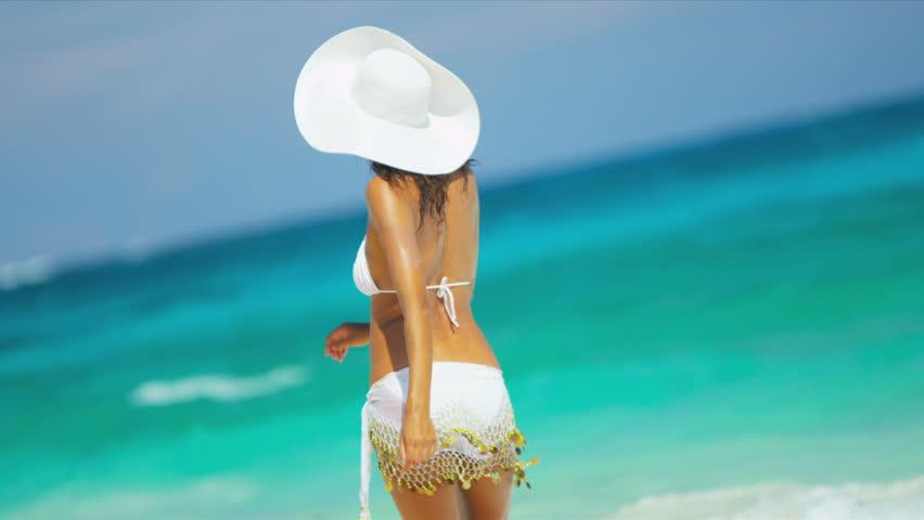 Beautiful carefree Latin American girl enjoying her beach lifestyle walking by aqua colored ocean shot on RED EPIC
