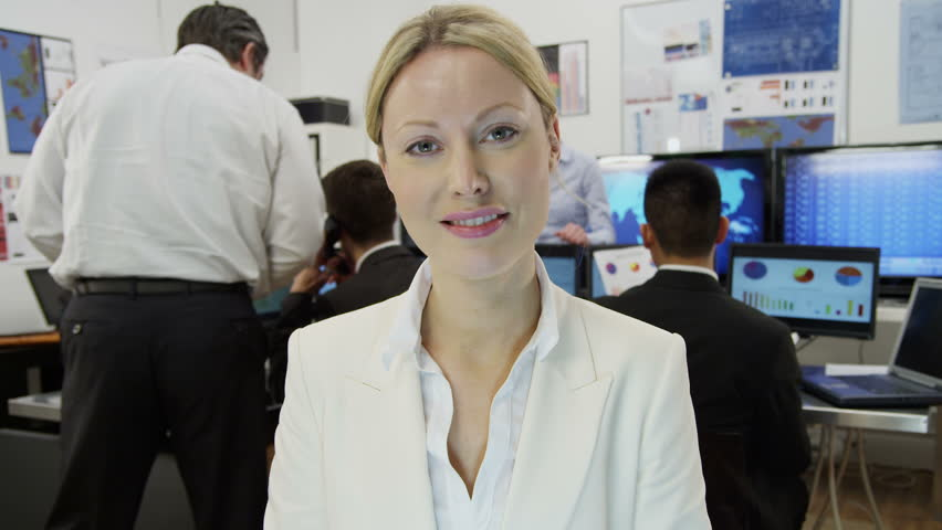 A beautiful young businesswoman is engaged in a video call with a client, as seen from the pov of the computer screen. She is sitting at her desk in a busy office filled with computers.