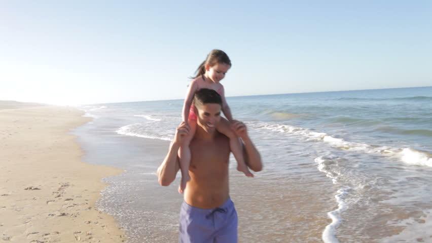 Father carrying daughter on shoulders running along beach. Shot on Canon 5d Mk2 with a frame rate of 30fps