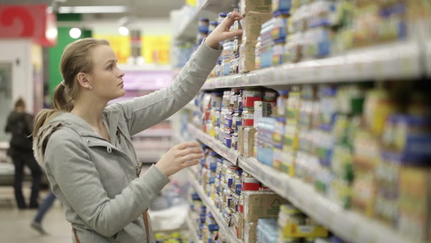 Young woman is choosing food for her child in the shopping center. No visible trademarks or logos. Middle shot with shoppers in background. | Shutterstock HD Video #3797912