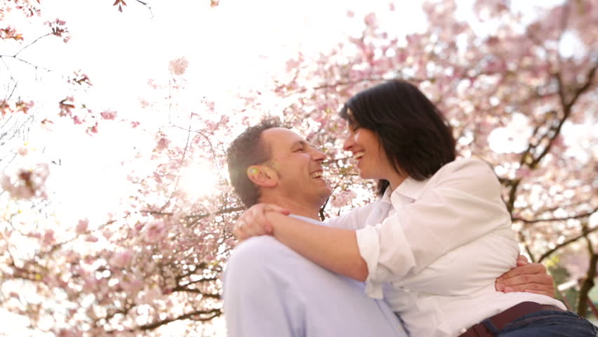Mature husband lifting is happy wife for a kiss under cherry blossoms, the couple enjoying spring sunshine