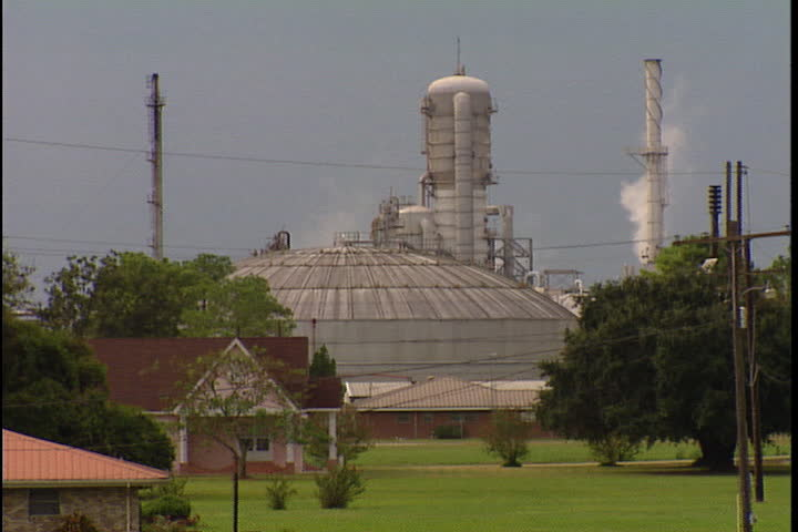 CONVENT, LOUISIANA - SEPTEMBER 4, 1999: Camera pans across smokestacks spewing smoke from Convent oil refineries and chemical plants along River Road.