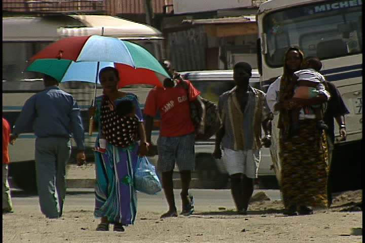 DAR ES SALAAM, TANZANIA - DECEMBER 1, 1998: Small group of people walking towards camera. A woman with a baby is carrying a huge umbrella.