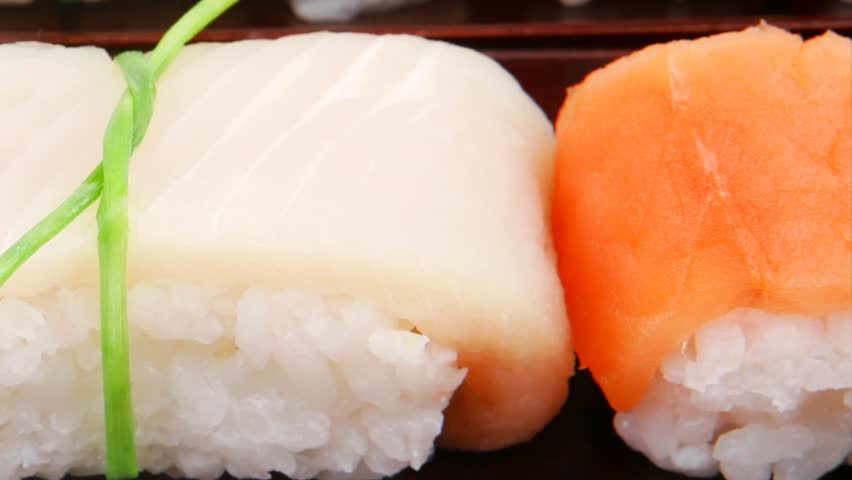 Japanese traditional cuisine - Different Types of Nigiri Sushi : Tuna (maguro) Salmon (sake) and Eel (unagi) with Wasabi and Ginger on bamboo mat 1920x1080 intro motion slow hidef hd